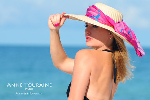 An ANNE TOURAINE Paris™ extra large chiffon silk scarf tied around a straw hat with a fluffy knot