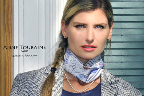 A stunning silk scarf tied close to the neck and combined with a pearl necklace: a true sign of Parisian elegance