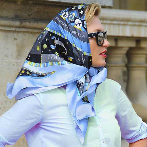 Astrology blue scarf featuring the twelve zodiac signs  by ANNE TOURAINE Paris™ scarves tied as a headscarf