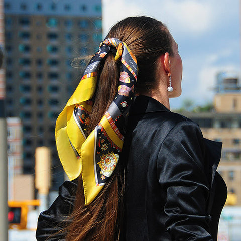 Astrology yellow and black scarf featuring the twelve zodiac signs  by ANNE TOURAINE Paris™ scarves tied on a ponytail