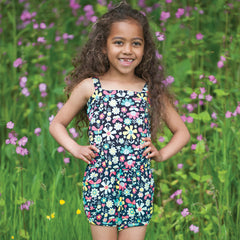 The Frugi Festival Playsuit features a bright garden print on navy.