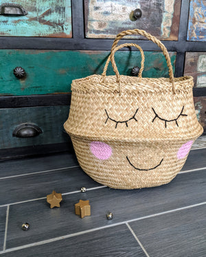 Beautiful seagrass woven storage basket with blushing smile motif