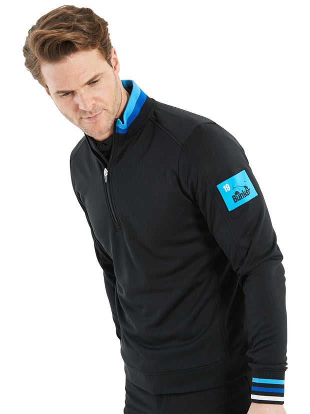 Bunker Mentality Black Golf Mid Layer Sweater with Tri Colour Rib on Collar and Cuffs and Blue patch on left arm - On Model