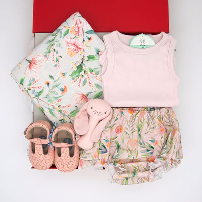 The feminine Summer Blooms baby hamper is the perfect combination of cute and practical. It features the prettiest outfit for little miss including handmade frilly bloomers with a co-ordinating tank top and pink leather t-bar shoes, ideal for all occasions throughout the festive season.  For swaddling a stunning Wattle muslin wrap has been included and for play the adorable Alimrose Bunny hand rattle.  All items are beautifully presented in our chic, red, signature memory box. $159.00