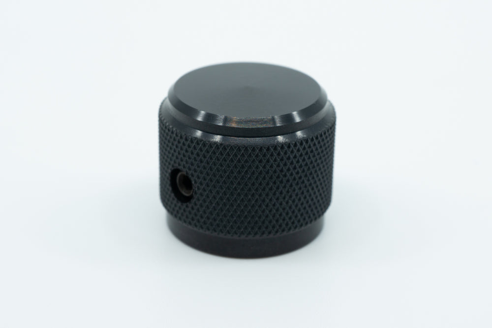 A macro photo of a black knurled aluminium encoder knob.