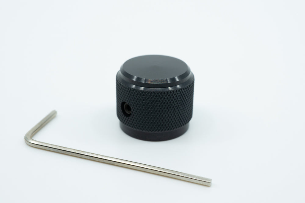 A photo of a black knurled aluminium encoder knob with an allen key.
