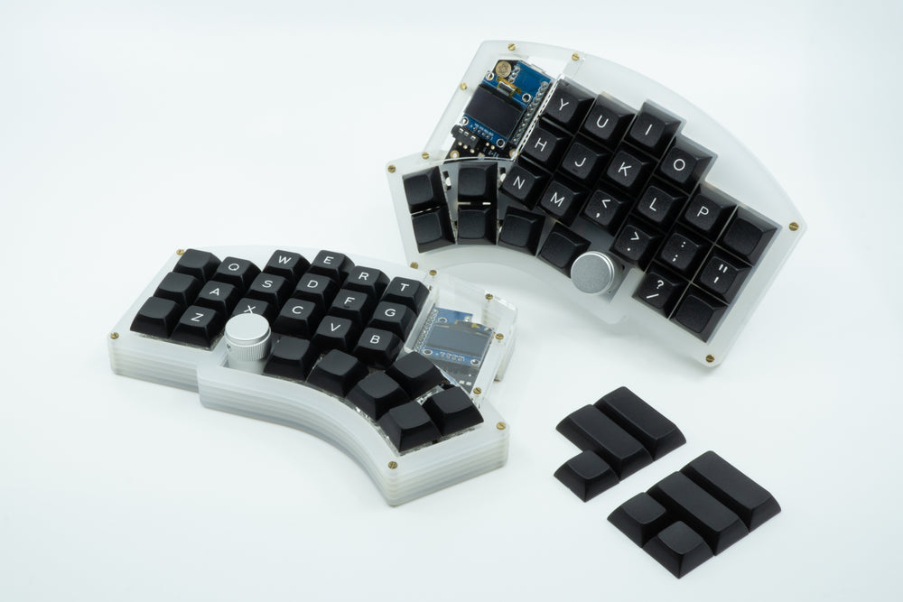 A Kyria keyboard showcasing black DSA keycaps, with legends for the alpha keys.