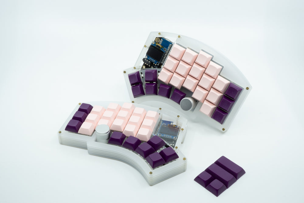 A Kyria showcasing purple and pink DSA keycaps, with light pink keycaps for the alpha keys and deep purple keycaps for the remainder.