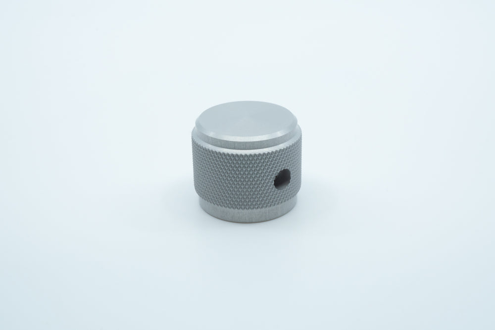 A macro photo of the side of a silver knurled aluminium encoder knob.