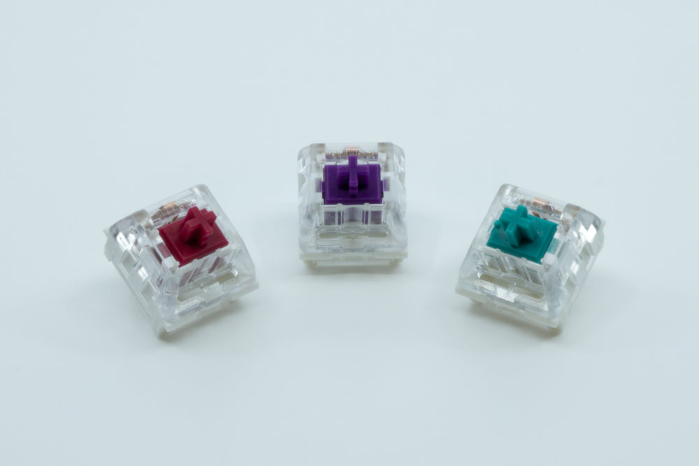 A front view of three Kailh Pro switches next to each other: Kailh Pro Burgundy, Purple and Light Green.