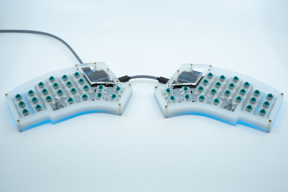 Load image into Gallery viewer, Both halves of a Kyria in a frosted high profile case, showing subtle blue underglow, without keycaps.