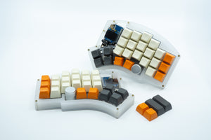 A Kyria showcasing sculpted SA keycaps, with the alphas being a creme color and the side and thumb cluster keycaps a mix of orange and gray.