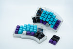 A Kyria showcasing SA keycaps with the alphas being brith blue, the outer rows deep purple and the thumb cluster being black.