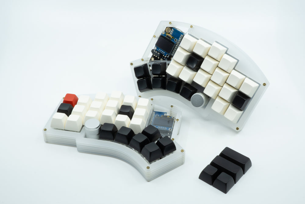 A Kyria showcasing sculpted SA keycaps, with the legends being white, with the homing keycaps and thumb cluster keycaps being black and a single red escape key.