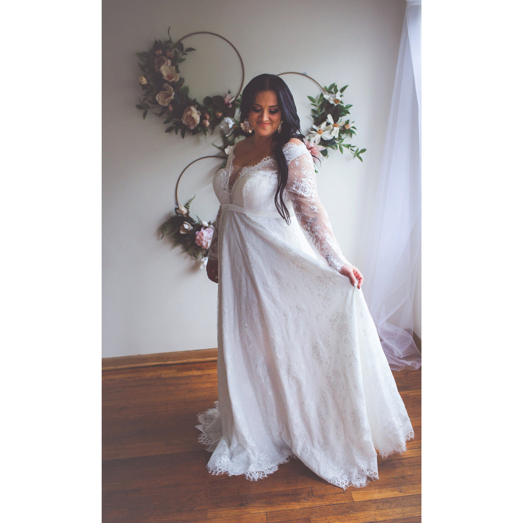 Bride holding out skirt of a line wedding dress
