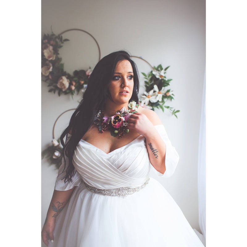 three quarter view of plus size bride in pleated bodice, jeweled belt, and tulle skirt