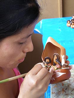 Manos Amigas Artisan hand painting a ceramic sculpture