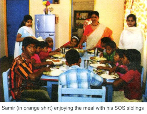 Sameer (in orange shirt) enjoying the meal with his SOS siblings