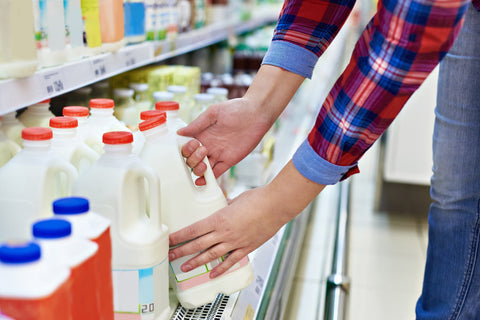 Person grabbing organic milk from the cold shelf