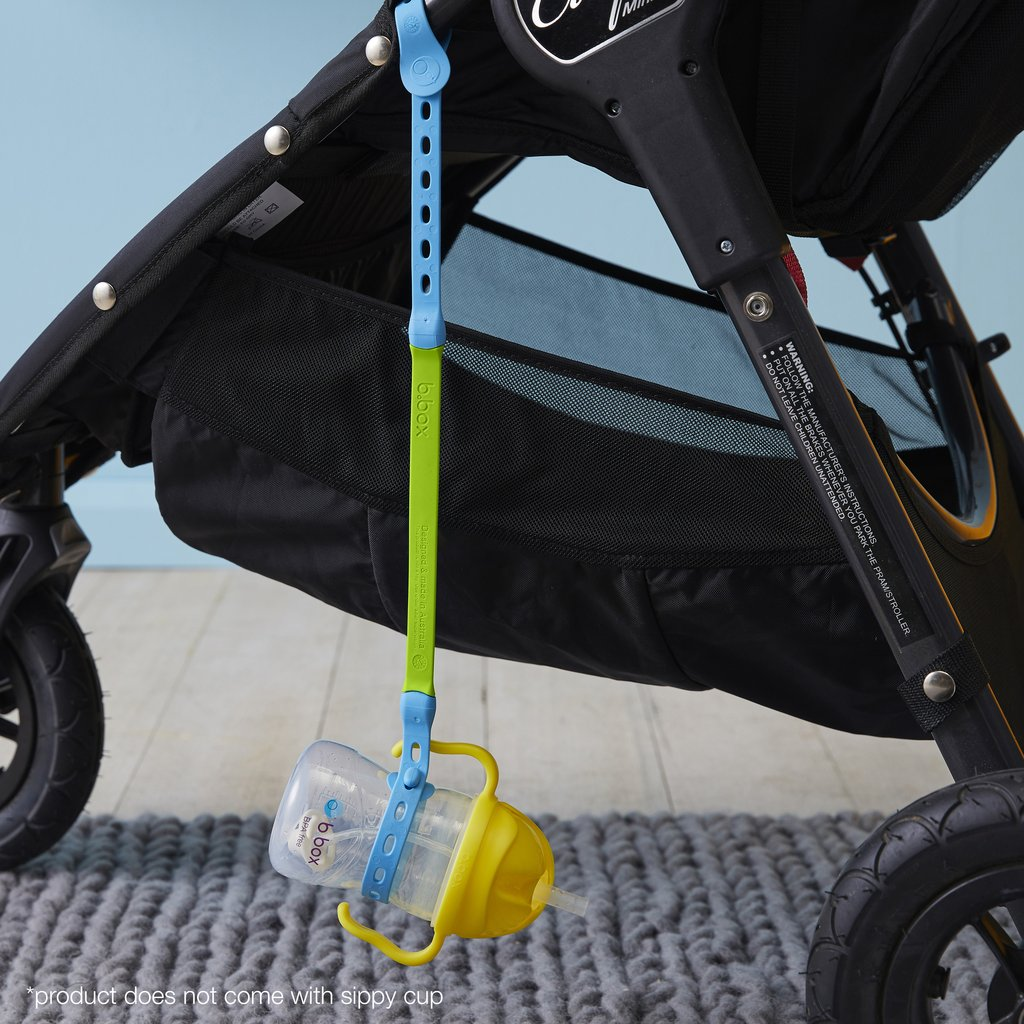Baby bottle connected to a strap and hanging off a pram