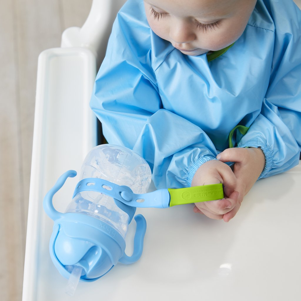 A child holding a Connect-A-Cup strap ad is connected to a baby bottle