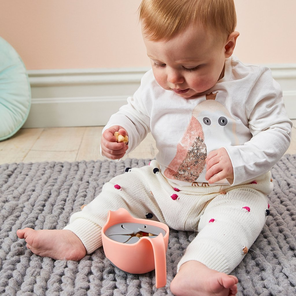 Baby using a bowl with straw