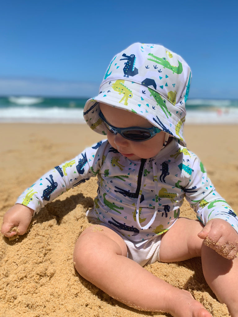 Child sitting on a sandy beach wearing a Bambooty Swim Hat, Swim Rashie and a Swim Nappy
