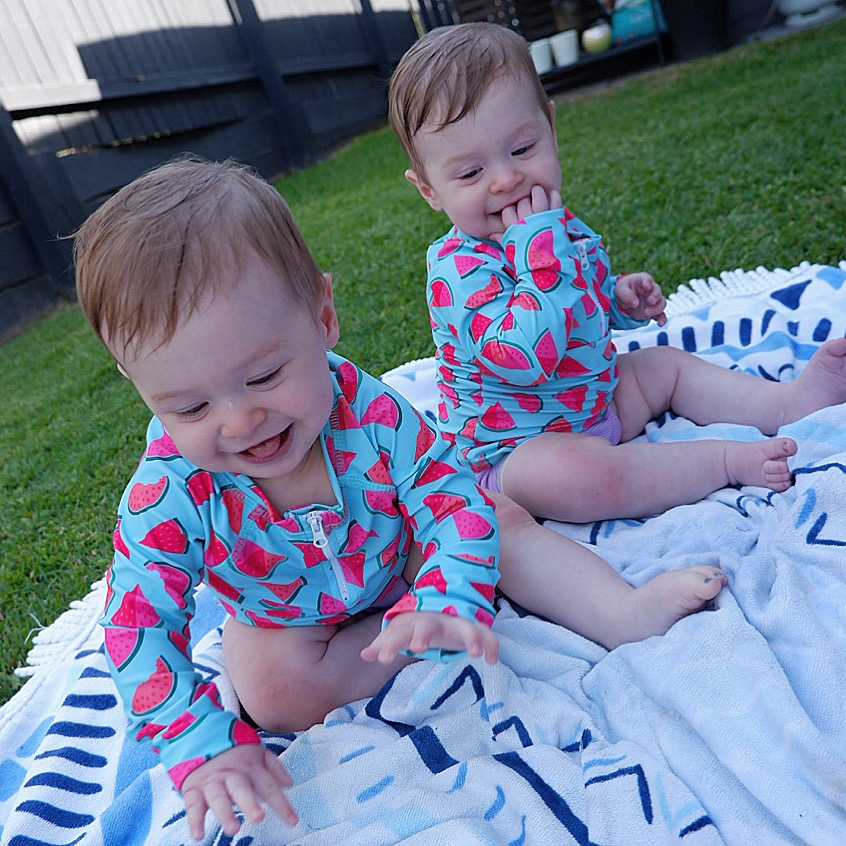 Infants sitting on a rug wearing Bambooty Swim Rashies and Swim Nappies
