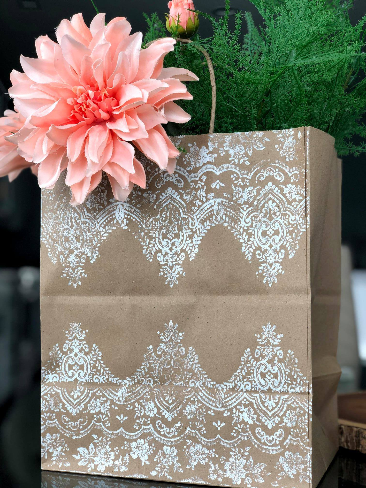 A Kraft bag with a white stamped pattern on the outside. Sticking out of the bag is a large pink flower and some greens.