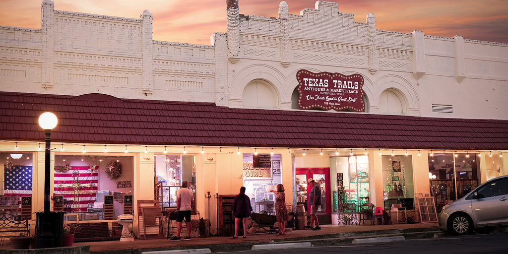 Texas Trails Antique and Marketing place store front shot with sun setting.