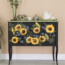 Load image into Gallery viewer, Sunflower Fields furniture decal by Redesign placed on a black buffet table. The design consists of 12 sunflower heads, extra greens and delicate blue blossoms.
