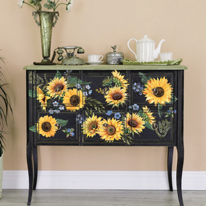 Sunflower Fields furniture decal by Redesign placed on a black buffet table. The design consists of 12 sunflower heads, extra greens and delicate blue blossoms.