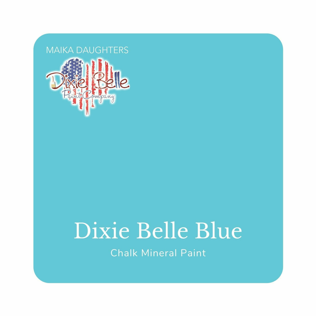 "A bright medium blue swatch in a square shape with rounded corners. At the bottom, and centered inside of the swatch, are the words: Dixie Belle Blue. Chalk Mineral Paint. And on the upper left hand corner, inside of the swatch is the word ""Maika Daughters"" and the logo for Dixie Belle Paint Company in the shape of a heart with the colors of the American Flag."