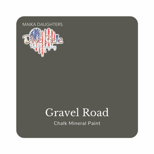 "A dark gray swatch in a square shape with rounded corners. At the bottom, and centered inside of the swatch, are the words: Gravel Road. Chalk Mineral Paint. And on the upper left hand corner, inside of the swatch is the word ""Maika Daughters"" and the logo for Dixie Belle Paint Company in the shape of a heart with the colors of the American Flag."