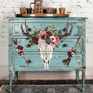 A blue distressed painted 3-drawer dresser with an image of a deer skull and two arrows, each with flowers is up against a white washed brick wall. A ceramic tray with a matching ceramic pitcher with cups sits on top of the dresser.