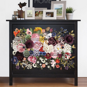 Black dresser with a cluster of flowers decal on the drawers. On top are some frame and a sign that says