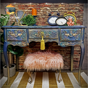 A painted blue dresser with lots of combination of colors throughout. A fluffy pink chair under it, and several items on top to stage it (a bust with a necklace), a candle on a candle stick, a bouquet of roses, and 3 vintage alarm clocks. Under the desk is a striped rug (white and gold). The the left and indoor plant in a pot. And behind it a stylish brick wall.