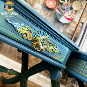 A close up of a blue night stand with a very fancy drawer. Various molds used and painted and one large flower in the middle, with elegant crystals.