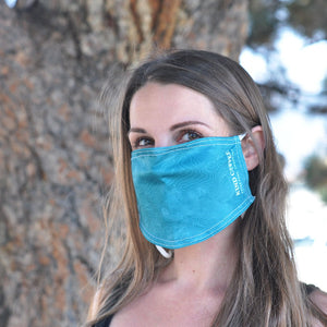 "Model wearing teal face mask with a topographical map of Estes Park, Colorado. ""Kind Coffee"" inscription"
