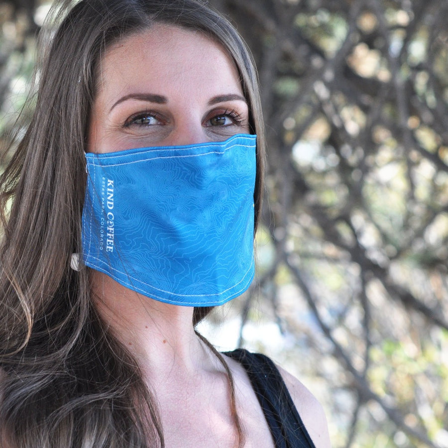 "Model wearing blue face mask with a topographical map of Estes Park, Colorado. ""Kind Coffee"" inscription"
