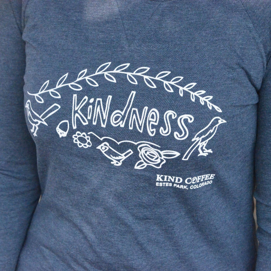 "Blue long sleeve shirt, ""Kindness"" and ""Kind Coffee, Estes Park Colorado"", drawings of birds and flowers"