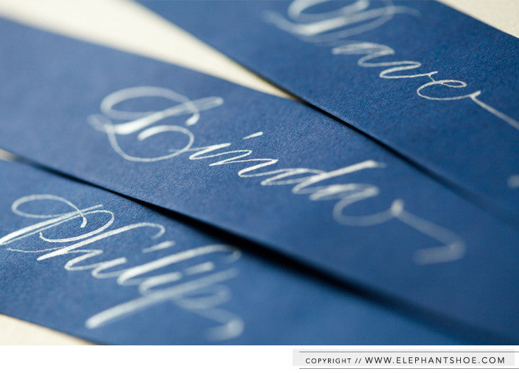 Guest names written in calligraphy and wrapped around each menu card // Photo by: Blackframe Photography