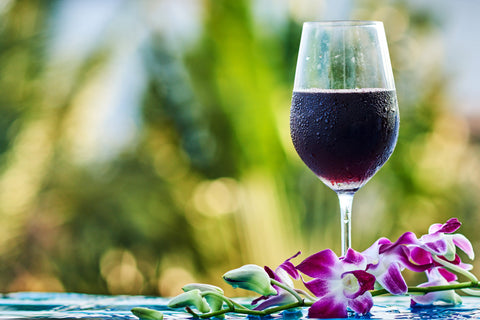 Chilled glass of red wine next to flowers