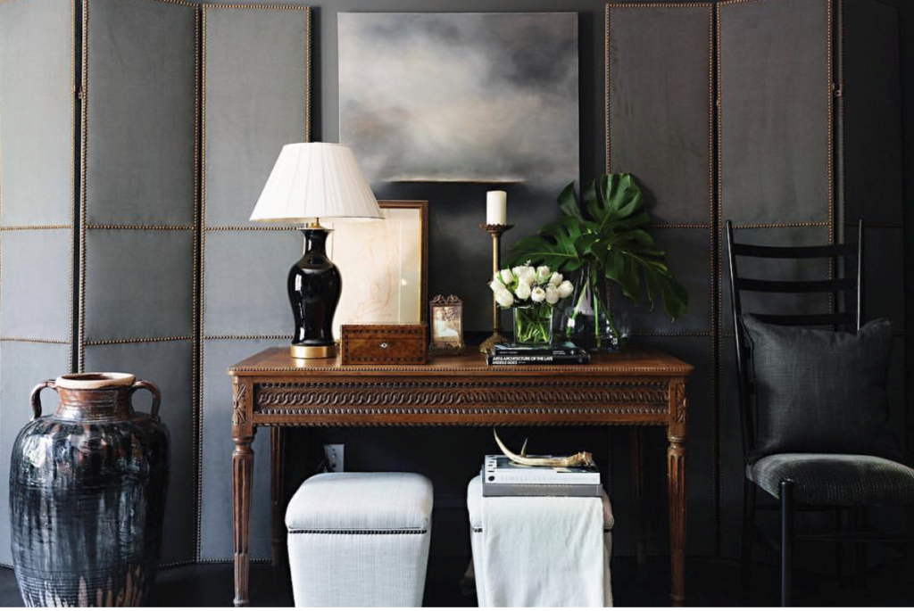 We love to see the pairing of a dark carved antique console with pretty modern upholstery and art.