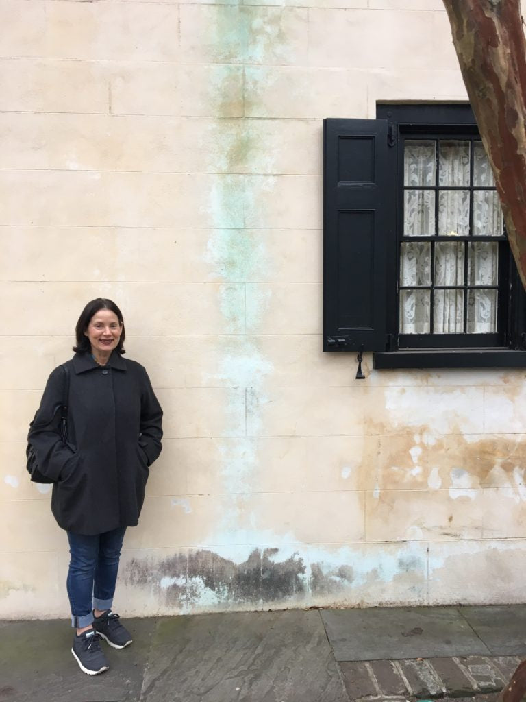 Barbara Sussberg, posing in front of an old house that is reminiscent of one of her textured paintings