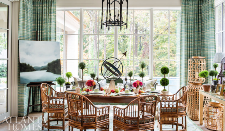 "Rattan is hot! <a href=""https://www.margaretkirklandinteriors.com/"" target=""_blank"">Margaret Kirkland</a> adds a liberal dose of it here in the breakfast room and then tempers it with a serene landscape by Andrea Costa and plenty of green topiaries."