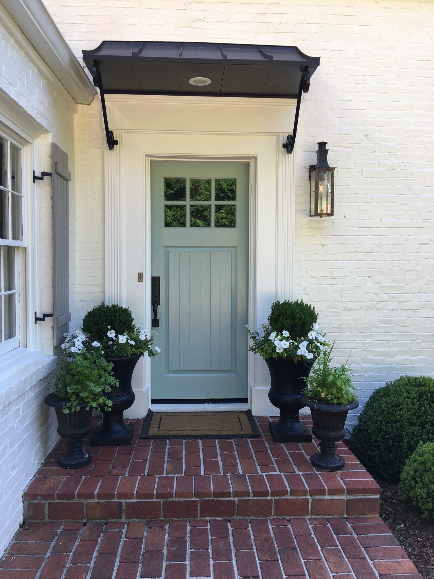 Pssst: Want to know the paint colors? Meg is sharing the secret: All from Sherwin Williams, the outside is Alabaster, the shutters are Pavestone and the front door is Wyeth Blue.