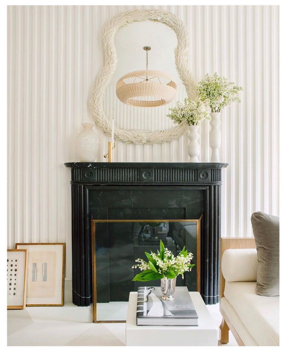 More unexpected contrasts: The classic black marble mantel reflecting a contemporary rattan fixture in the very cool plaster mirror, from Cox London. Patrick Cline Photography