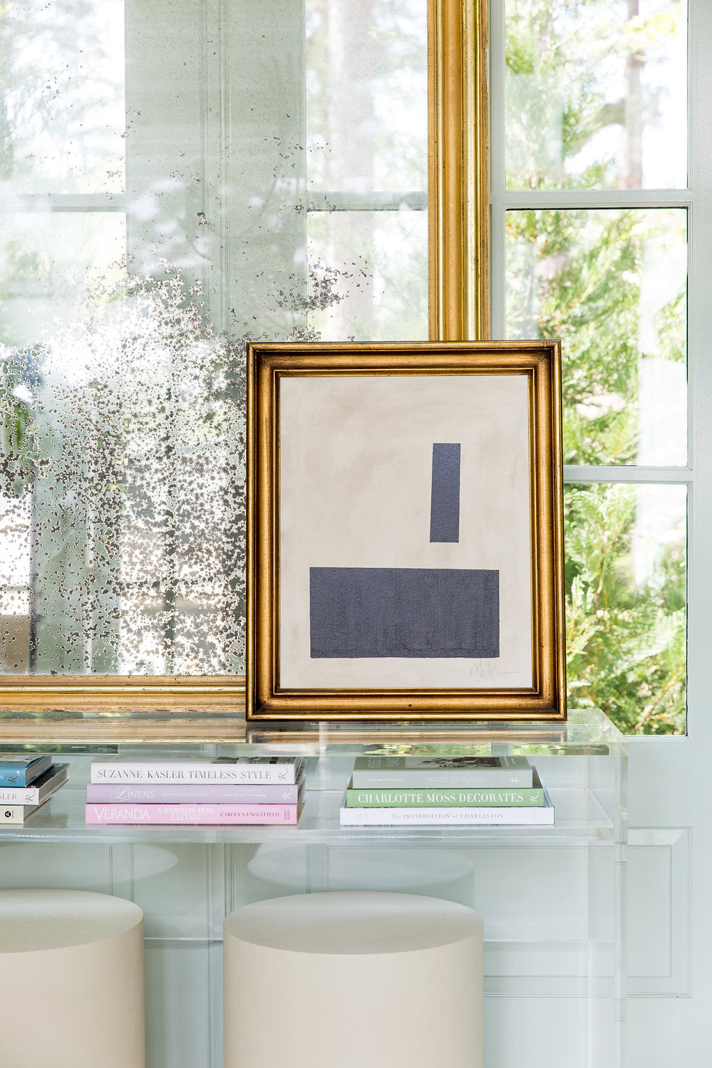 This one is so pretty, with the layering of books on the clean and graphic lucite console layered against art and an antique mirror.