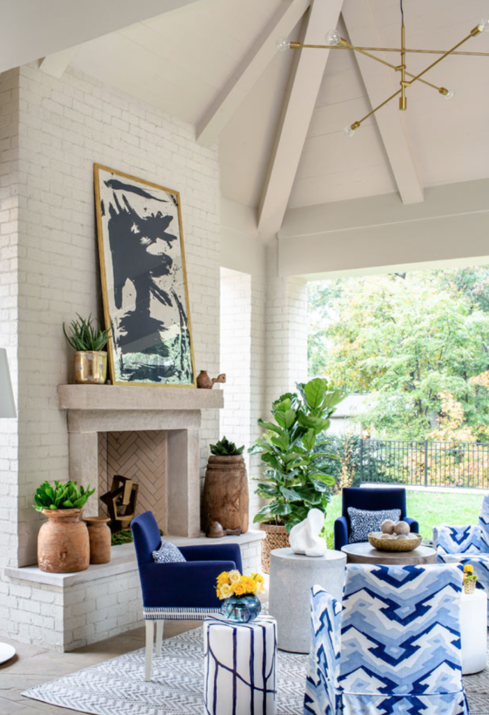 "The porch, perfect for all-year lounging, gets its chic on with a geometrical chandelier, jazzy Thibaut upholstery and an original painting on mirror by Stacy Milburn. Design by <a href=""http://kkongdesigns.com/index.html"" target=""_blank"">Kristen Kong</a>."